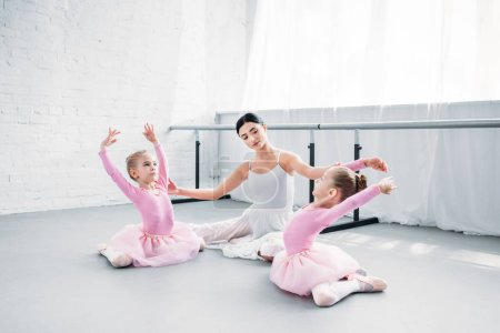 Photo for Ballet teacher with kids in tutu skirts sitting and stretching in ballet school - Royalty Free Image