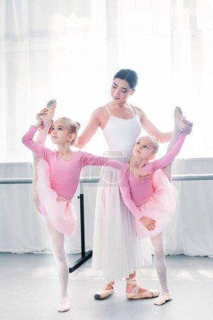 young ballet teacher exercising with small ballerinas in ballet school
