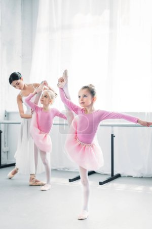 Photo for Ballet teacher exercising with small dancers in ballet school - Royalty Free Image