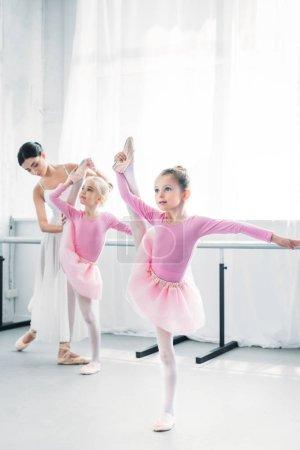 ballet teacher exercising with small dancers in ballet school
