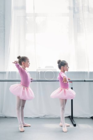 side view of cute small ballet dancers exercising in ballet school