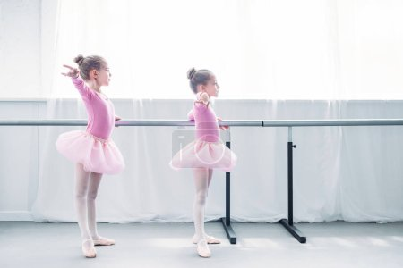 side view of beautiful little kids in pink tutu skirts practicing ballet in ballet studio
