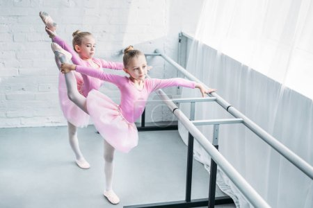 high angle view of cute little ballet dancers stretching in ballet school