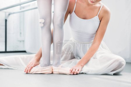 cropped shot of ballet teacher practicing ballet with little student in pointe shoes