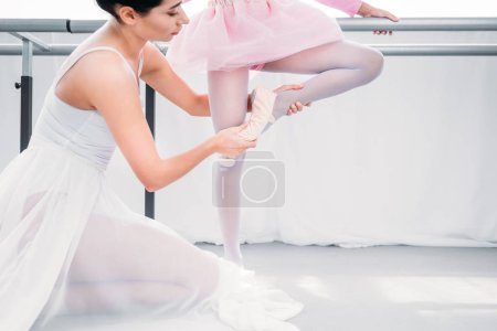 Photo for Cropped shot of ballet teacher training with little student in ballet school - Royalty Free Image