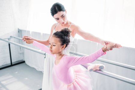 cute african american child in pink tutu exercising with teacher in ballet school
