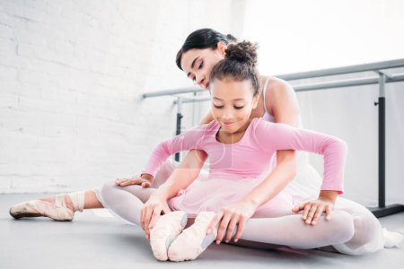 smiling african american child in pink tutu stretching while training with teacher in ballet school