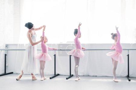 side view of ballet teacher exercising with children in ballet school