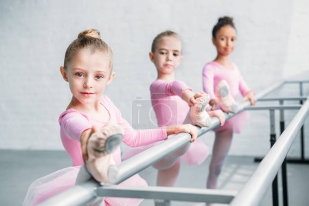beautiful children looking at camera while stretching in ballet school