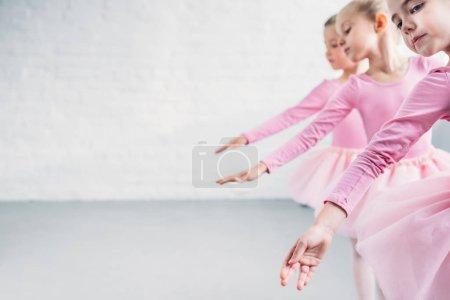 side view of graceful little ballerinas dancing together in ballet school