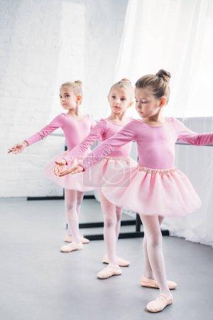 Photo pour Adorables petites ballerines pratiquant ensemble dans un studio de ballet - image libre de droit