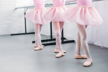Photo for Low section of cute little kids in pink tutu skirts and ballet shoes dancing in studio - Royalty Free Image