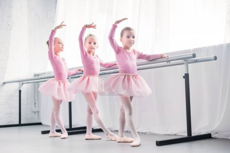 Photo for Full length view of adorable little children in pink tutu skirts dancing in ballet studio - Royalty Free Image