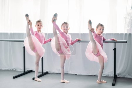 beautiful little ballet dancers exercising and looking at camera in ballet school