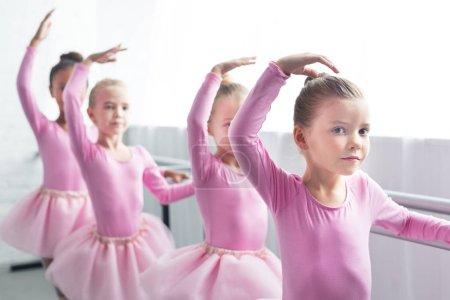 Photo pour Beaux enfants en jupes tutu rose danse à l'école de ballet - image libre de droit