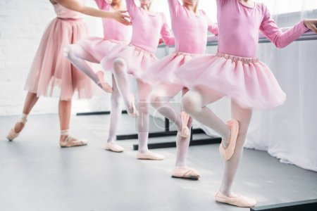 cropped shot of kids in pink tutu skirts practicing ballet with teacher in ballet school