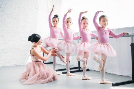 young woman teaching adorable children dancing in ballet school