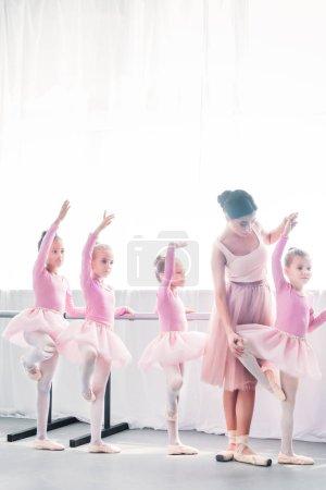 young woman teaching adorable kids dancing in ballet school