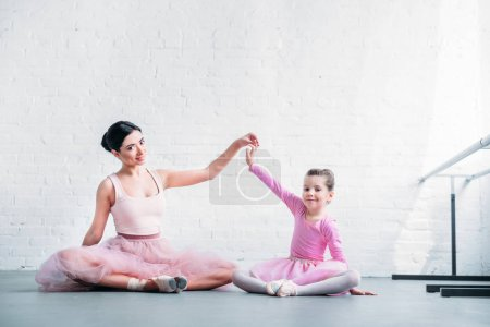 beautiful adult and little ballerinas in pink tutu skirts sitting and smiling at camera in ballet studio