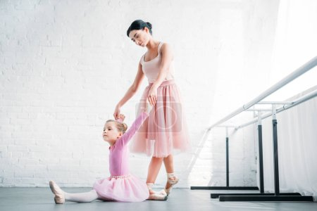 young ballet teacher looking at child in pink tutu stretching in ballet school