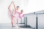beautiful adult and little ballerinas stretching and smiling at camera in ballet school