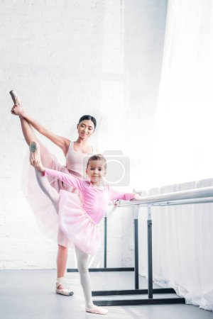 Photo for Smiling young ballet teacher looking at little student stretching and looking at camera in ballet studio - Royalty Free Image