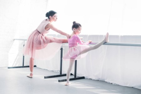 young ballet teacher looking at little student stretching in ballet studio