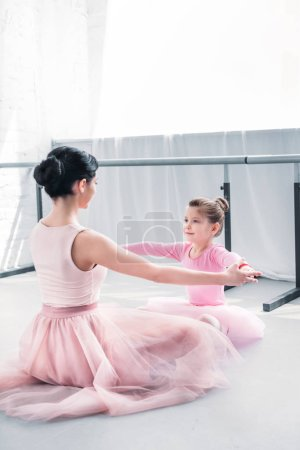 young ballet teacher and little student in pink tutu skirts training together in ballet school