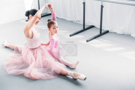 high angle view of ballet teacher and little student stretching together in ballet studio