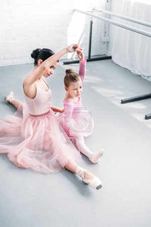 Photo for High angle view of ballet teacher and little student training together in ballet school - Royalty Free Image