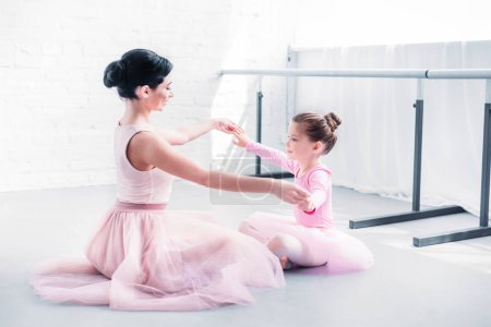 side view of ballet teacher and little student in pink tutu skirts sitting and holding hands while training in ballet school