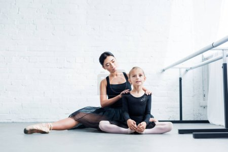 ballet teacher and little student in black clothing exercising together in ballet school