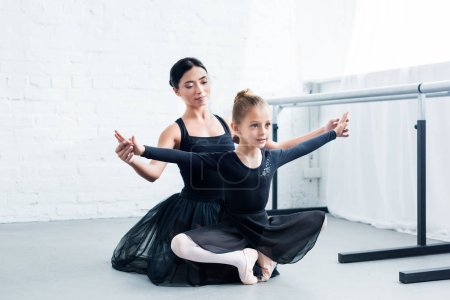young ballet teacher training cute flexible child in ballet school