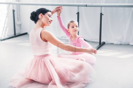 Photo for Smiling young ballet teacher and little student in pink tutu skirts training together in ballet school - Royalty Free Image