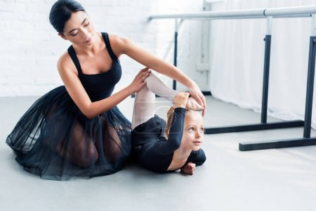 young ballet teacher and cute little student exercising together in ballet school