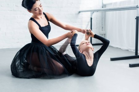 young ballet teacher training adorable flexible child in ballet school