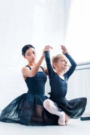 Photo pour Belle jeune ballet enseignant formation adorable souple enfant à l'école de ballet - image libre de droit