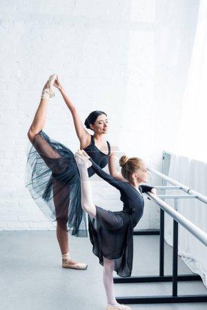 Photo pour Vue latérale du professeur de ballet jeune et étudiant petit étirement de l'ensemble à l'école de ballet - image libre de droit