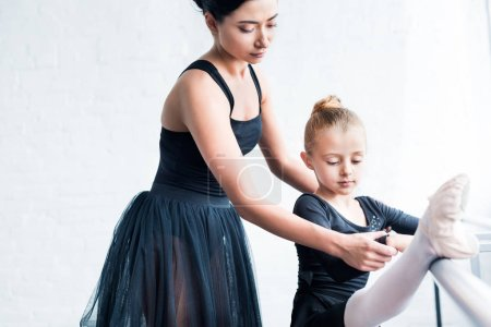 cropped shot of young ballet teacher training child in ballet school