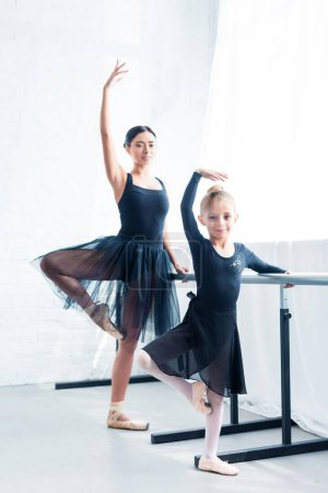 beautiful young ballet teacher and cute little student dancing together in ballet studio