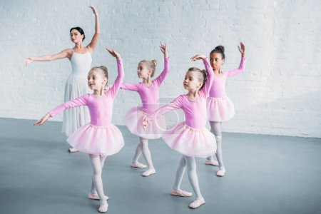 Photo for Adorable kids in pink tutu skirts practicing ballet with young teacher in ballet school - Royalty Free Image