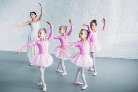 Photo pour Adorables enfants en tutu rose jupes pratiquant le ballet avec jeune professeur à l'école de ballet - image libre de droit