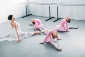 adorable little ballerinas and young teacher stretching and exercising together in ballet school