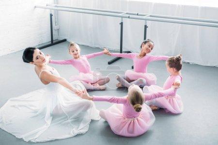 Photo pour Adorables petites ballerines et jeunes professeurs pratiquant ensemble dans une école de ballet - image libre de droit