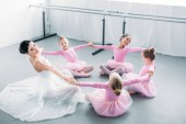 adorable little ballerinas and young teacher practicing together in ballet school