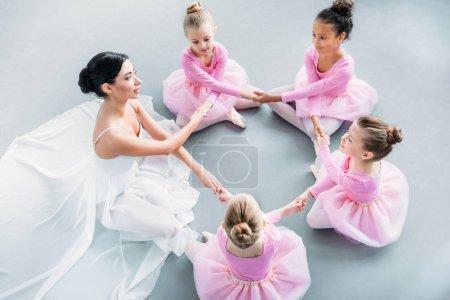 Photo pour Vue grand angle de petites ballerines et professeur de ballet s'exerçant ensemble à l'école de ballet - image libre de droit
