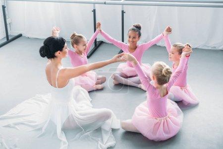 Photo pour Happy little ballerines et professeur de ballet, assis et tenant par la main à l'école de ballet - image libre de droit
