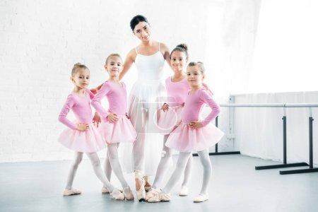 Photo pour Professeur de ballet avec de jolies petites ballerines souriant à la caméra à l'école de ballet - image libre de droit
