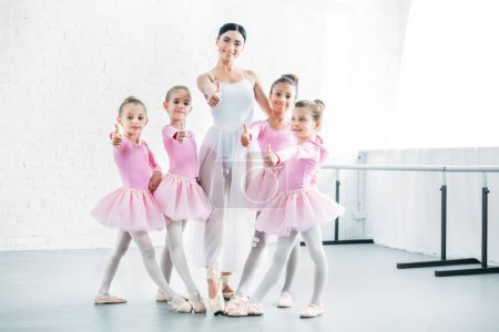 little ballerinas and ballet teacher showing thumbs up and smiling at camera in ballet school