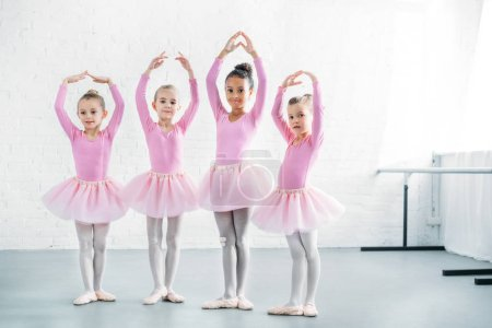 beautiful multiethnic kids in pink tutu skirts practicing ballet together